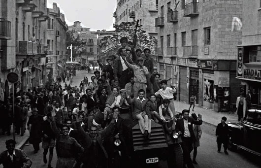 Jewish residents of Jerusalem ride a police car and wave what would become the Israeli flag as they celebrate the previous day's General Assembly vote recommending the partitioning of Palestine, Nov. 30, 1947. (Hans Pins/GPO via Getty Images)