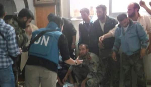 U.N. observers speak to members of the Free Syrian Army who claimed regime loyalists were responsible for the Houla massacre (Reuters/Houla News Network)