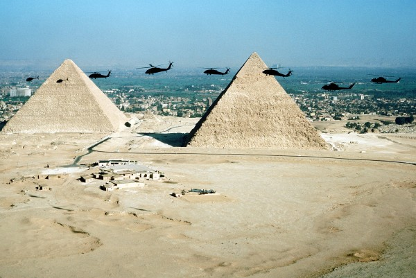 Military helicopters fly over the Great Pyramids of Giza outside of Cairo, Egypt