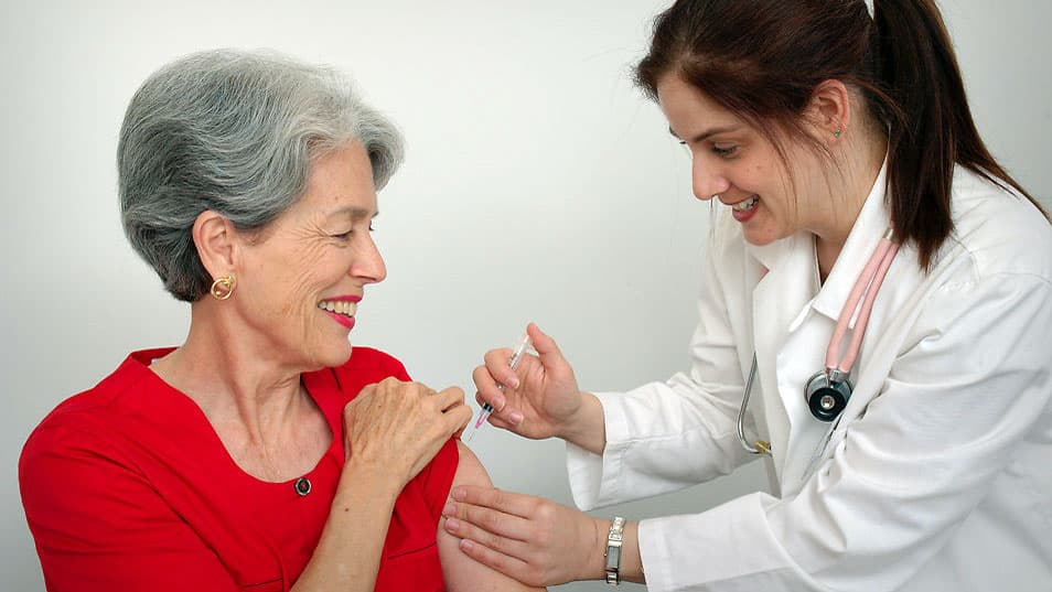 A senior woman receiving a vaccination from her doctor. (CDC/Public Domain)